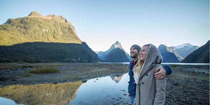 Couple enjoying mountain scenery, Milford Sound