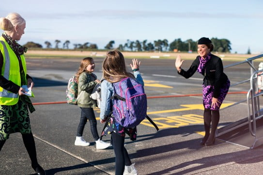 Children waving goodbye leaving an aircraft.