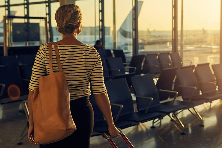 A woman walking with her luggage through the departure lounge of an airport.
